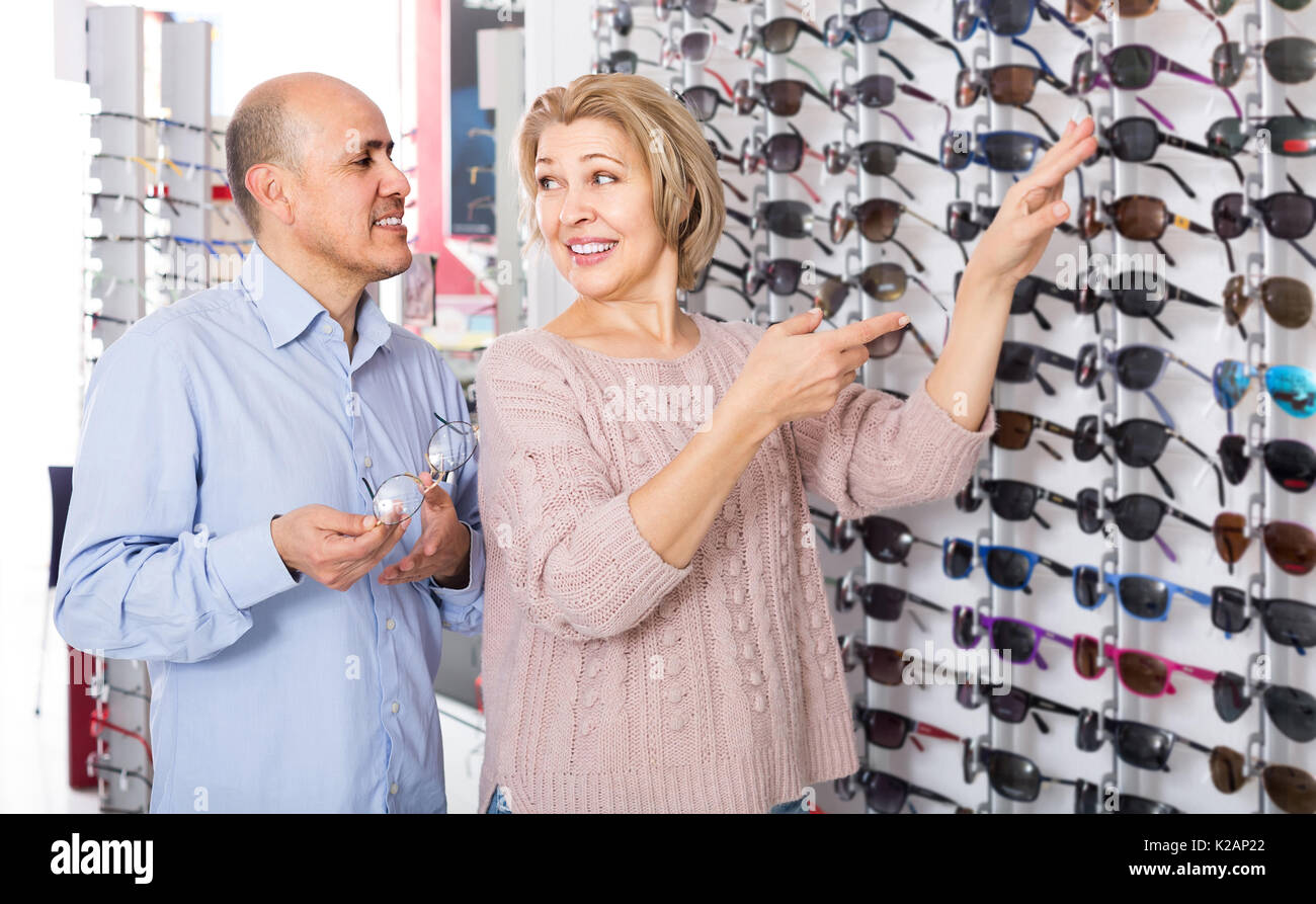 Senior couple trying spectacles frames and smiling near stand Stock ...