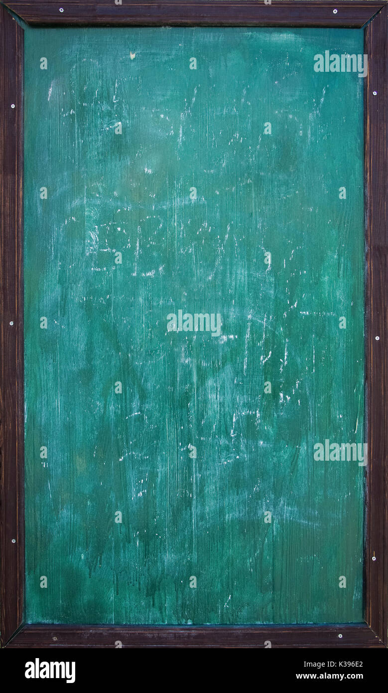 green blank chalkboard with wooden frame and traces of chalk writing