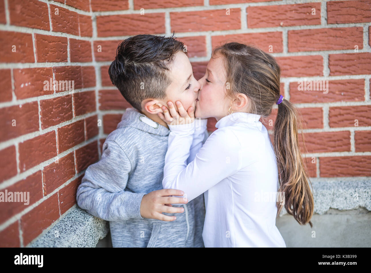 first love and kiss two happy cute kids meeting stock photo