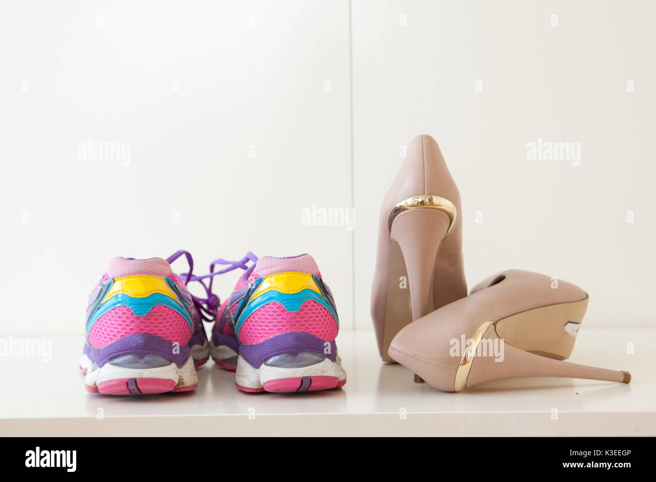 5477c59ef555 A pair of colorful sports shoes next to high heel stilettos Stock ...