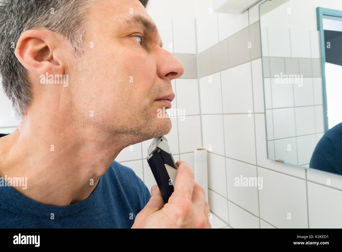portrait of a man looking in mirror trimming beard stock photo