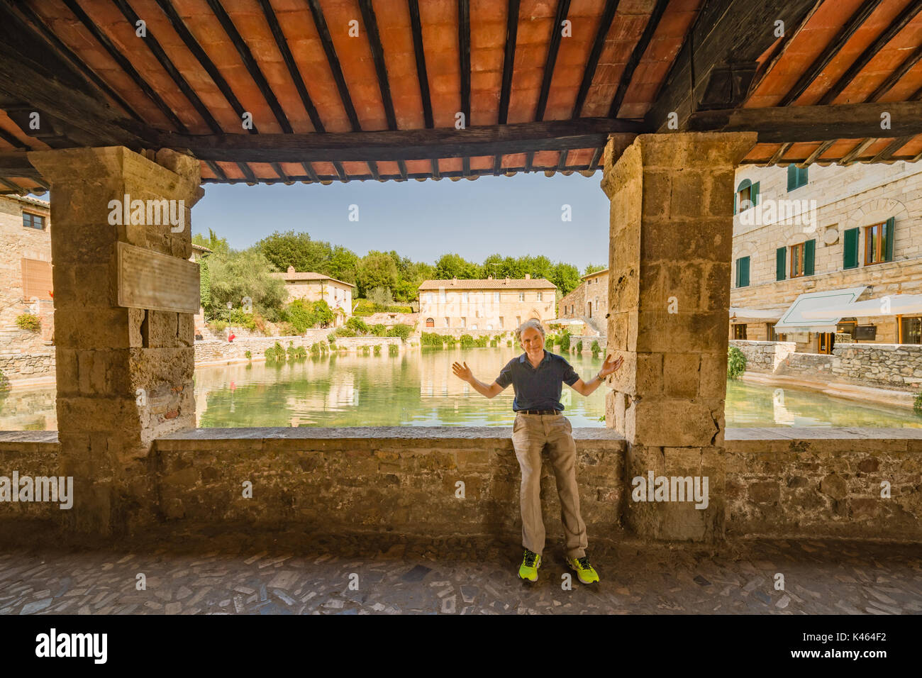 Mature man resting with open arms sitting on border of unusual