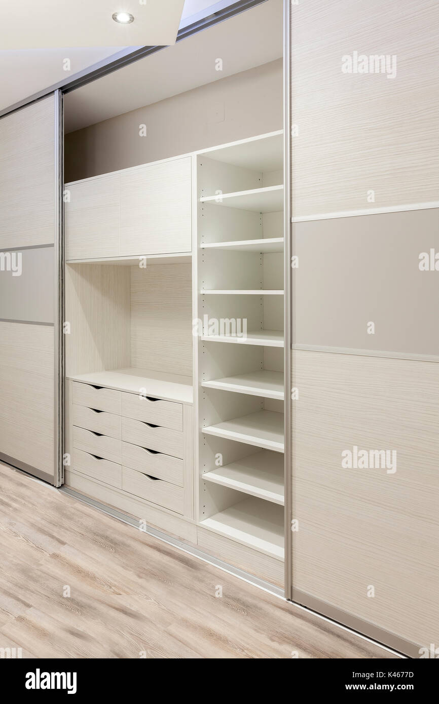 wardrobe with sliding doors with lots of shelves and drawers stock