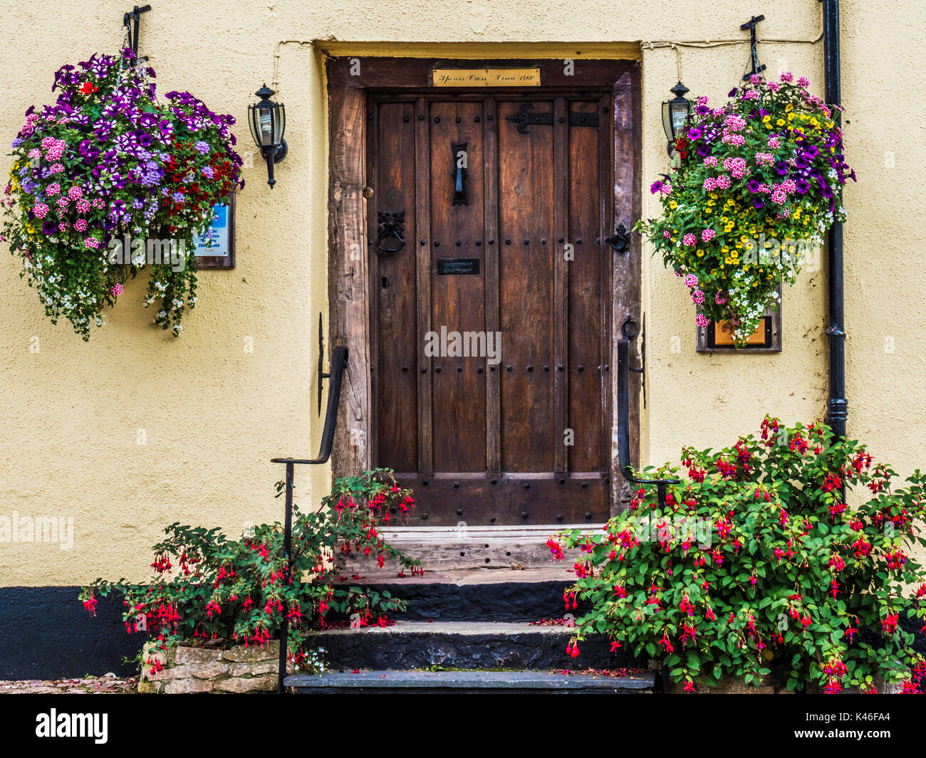 Old Wooden Front Door Surrounded By Colourful Flowers In Dunster High  Street Near Minehead, Somerset