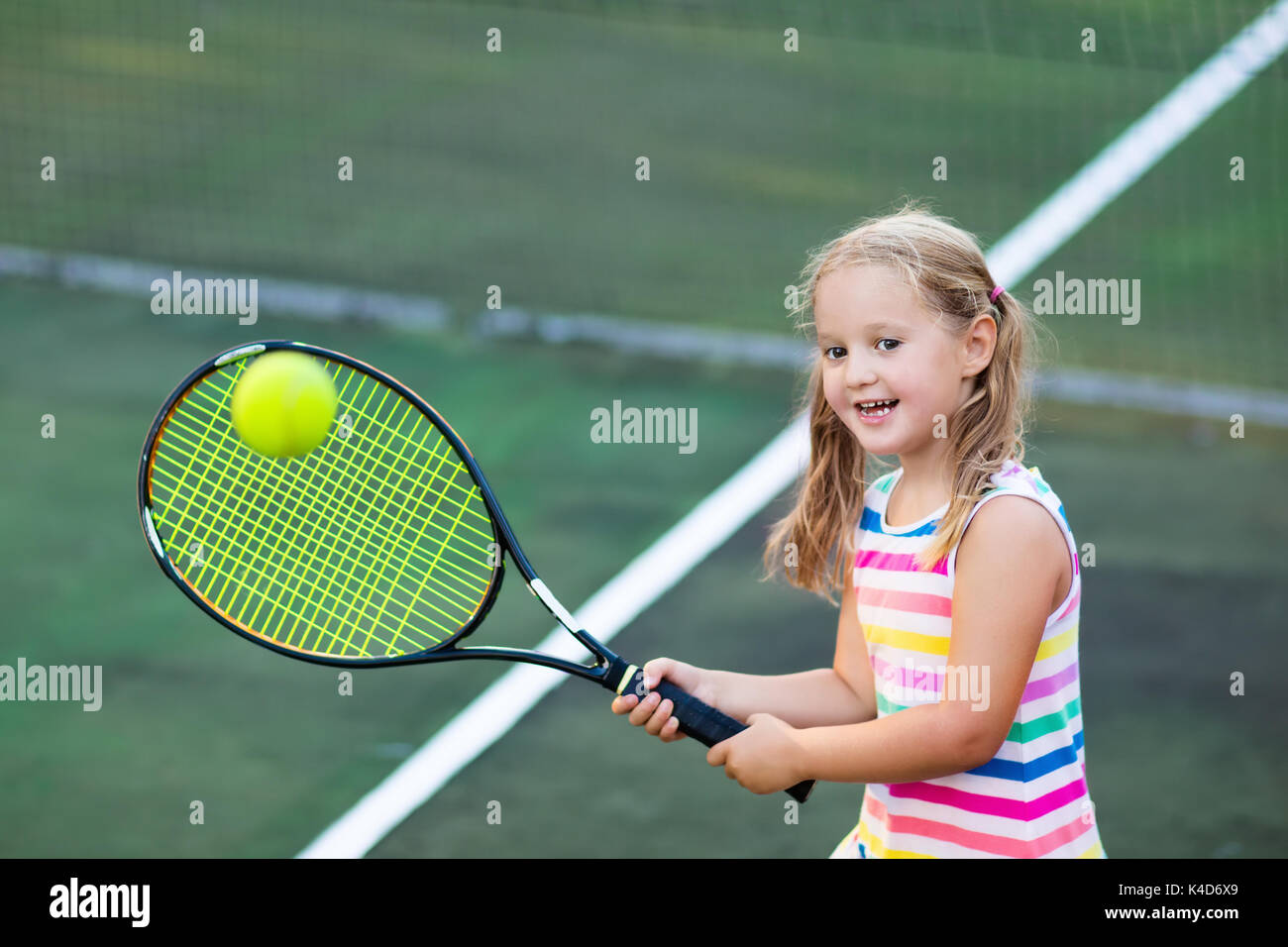 Child playing tennis on outdoor court. Little girl with ...