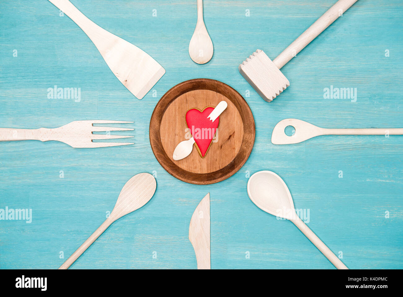 top view of various wooden kitchen utensils with pierced heart ...