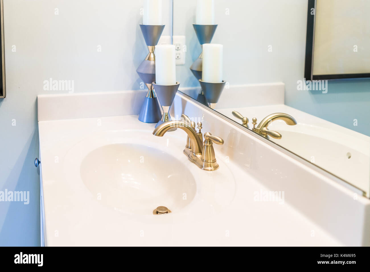Closeup of modern bathroom sink with white countertop, mirror and ...