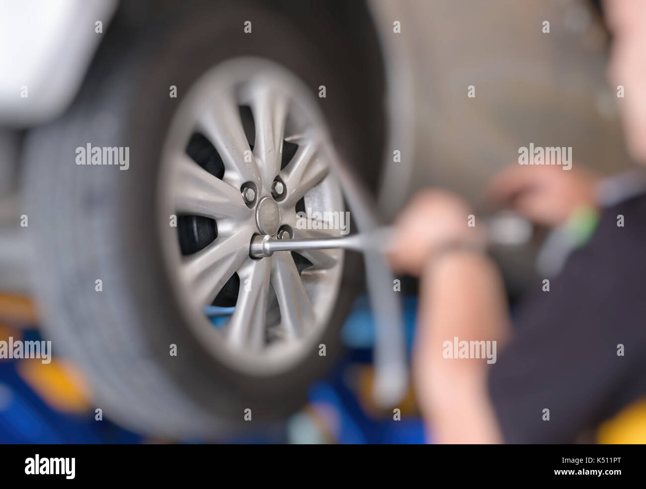 Mechanic Changing Car Wheel In Auto Repair Shop Serviceman Wrenching Spanner To Replace Vehicle Tyre Automobile Garage Fixing Checking Concept