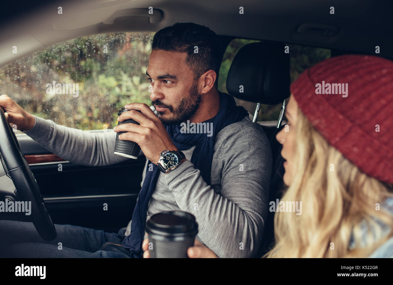 Young Man And Woman Traveling By Car And Having Coffee. Couple Drinking  Coffee While Driving A Car