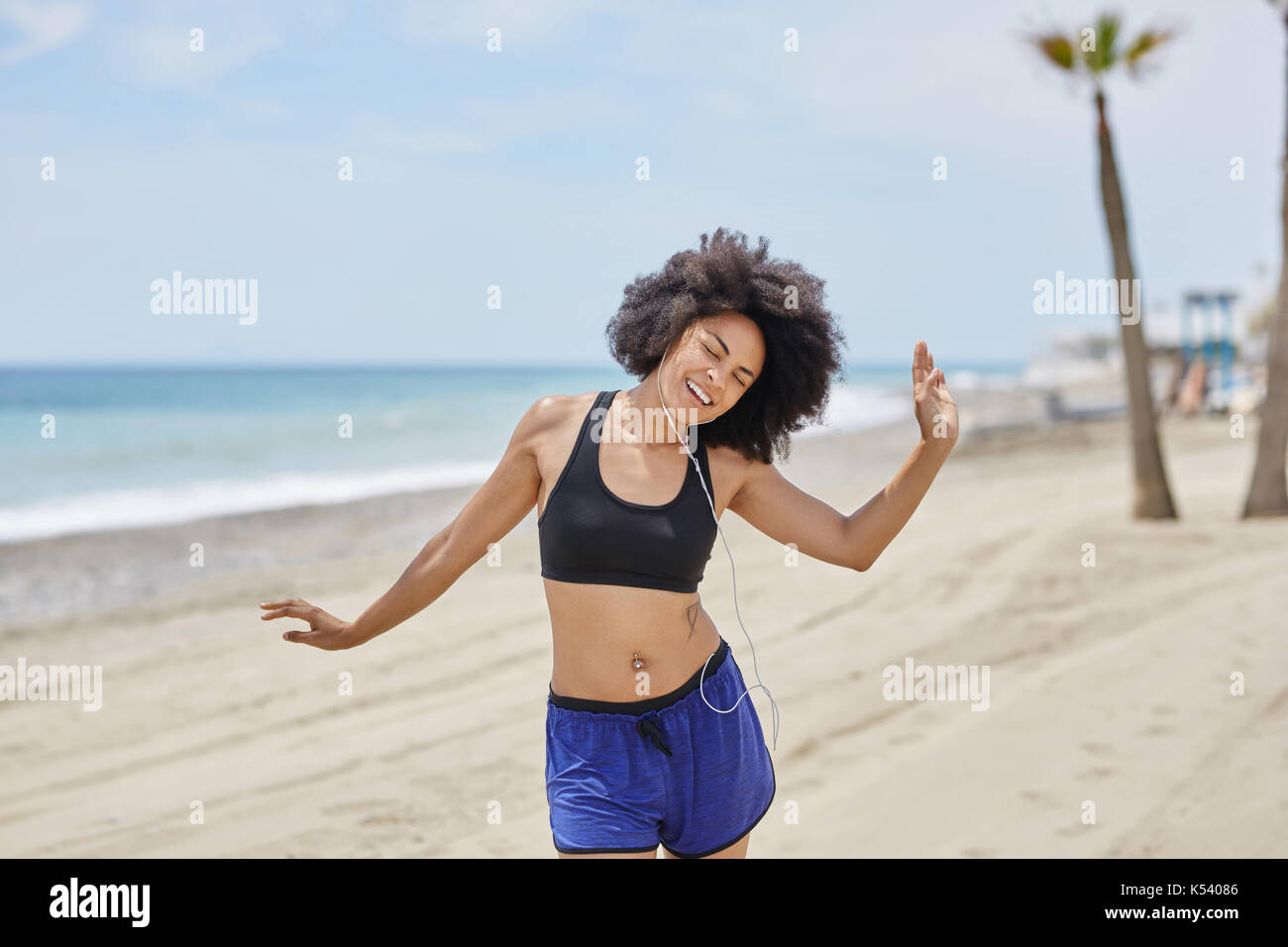 portrait of afro american woman listening music dancing on beach
