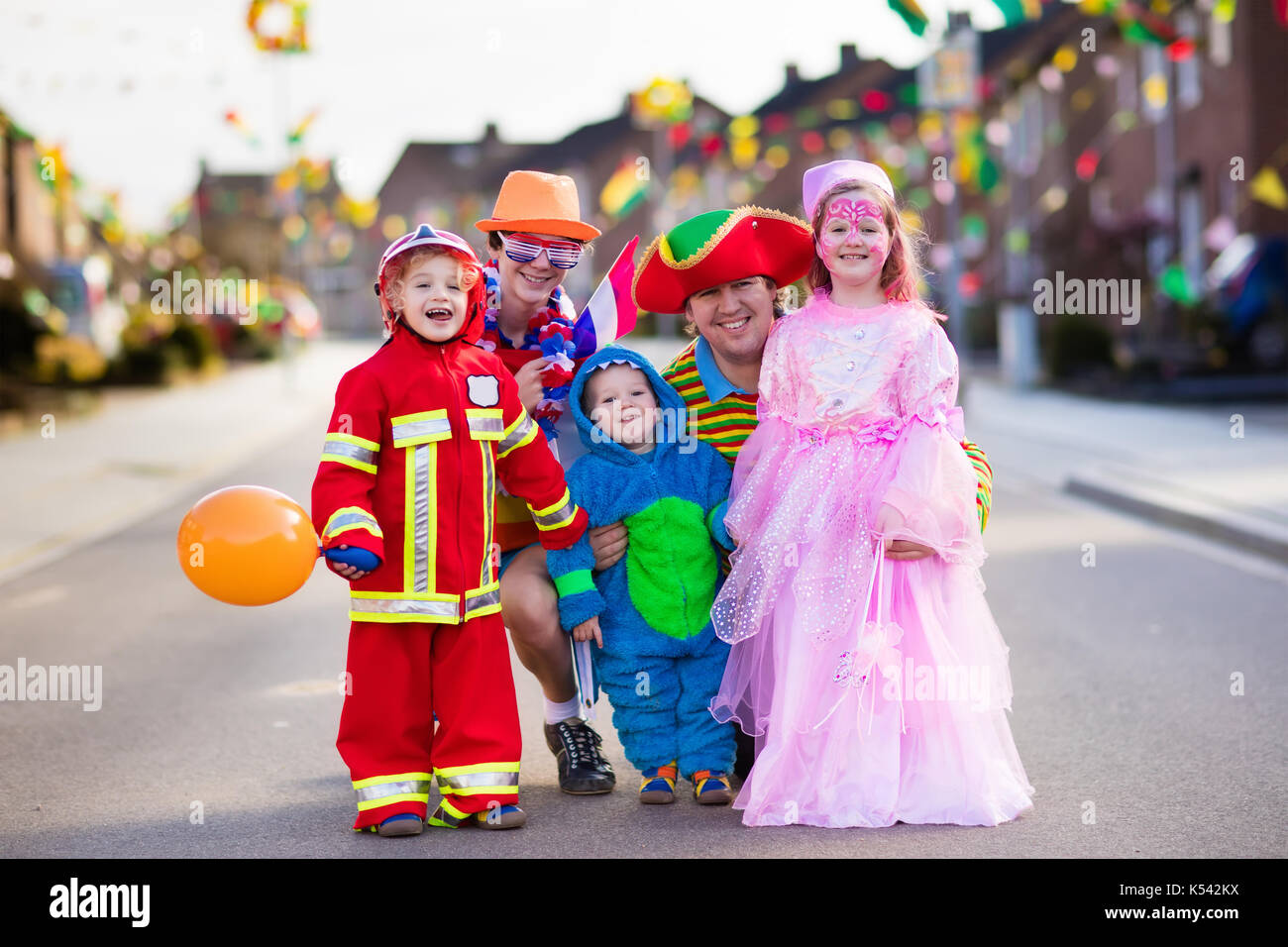 kids and parents on halloween trick or treat family in halloween costumes with candy bags walking in decorated street trick or treating baby and pre