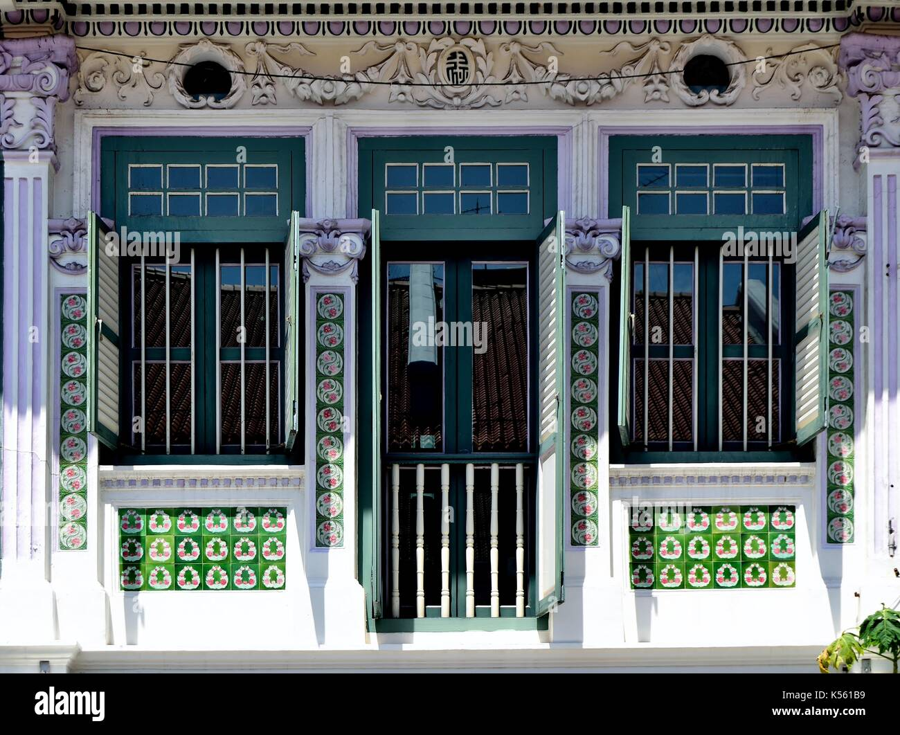 Traditional shop house exterior with green louvered shutters, ornate ...