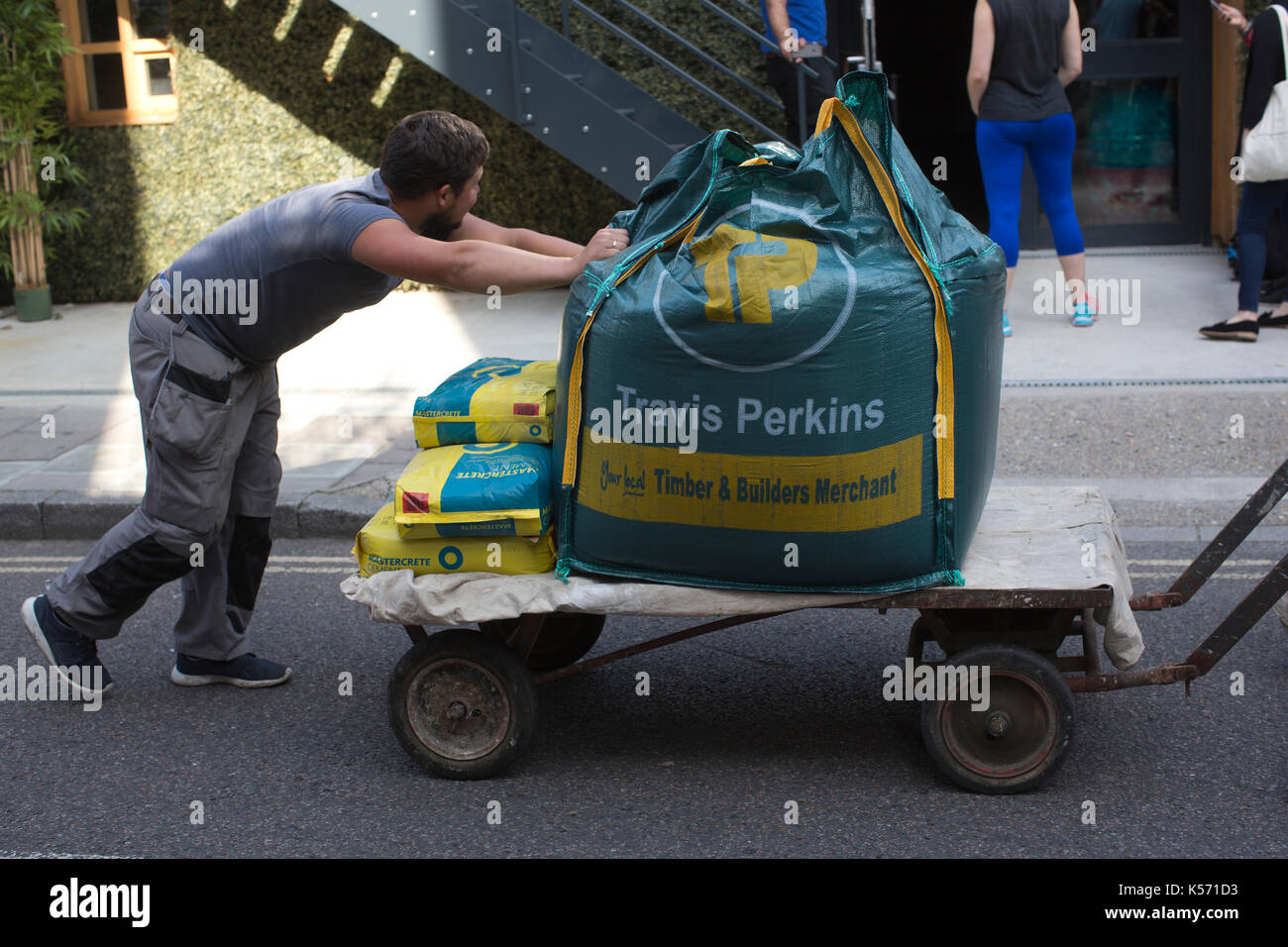 Travis perkins stock photos travis perkins stock images alamy man pushing trolley with travis perkins timber builders merchant cement and sand for construction rubansaba