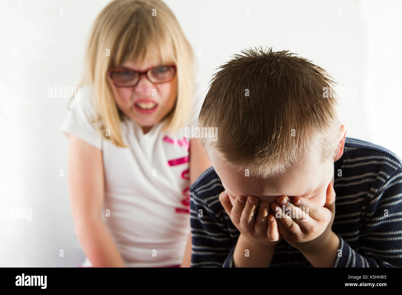 young boy sad as he is being picked on by an angry girl stock photo