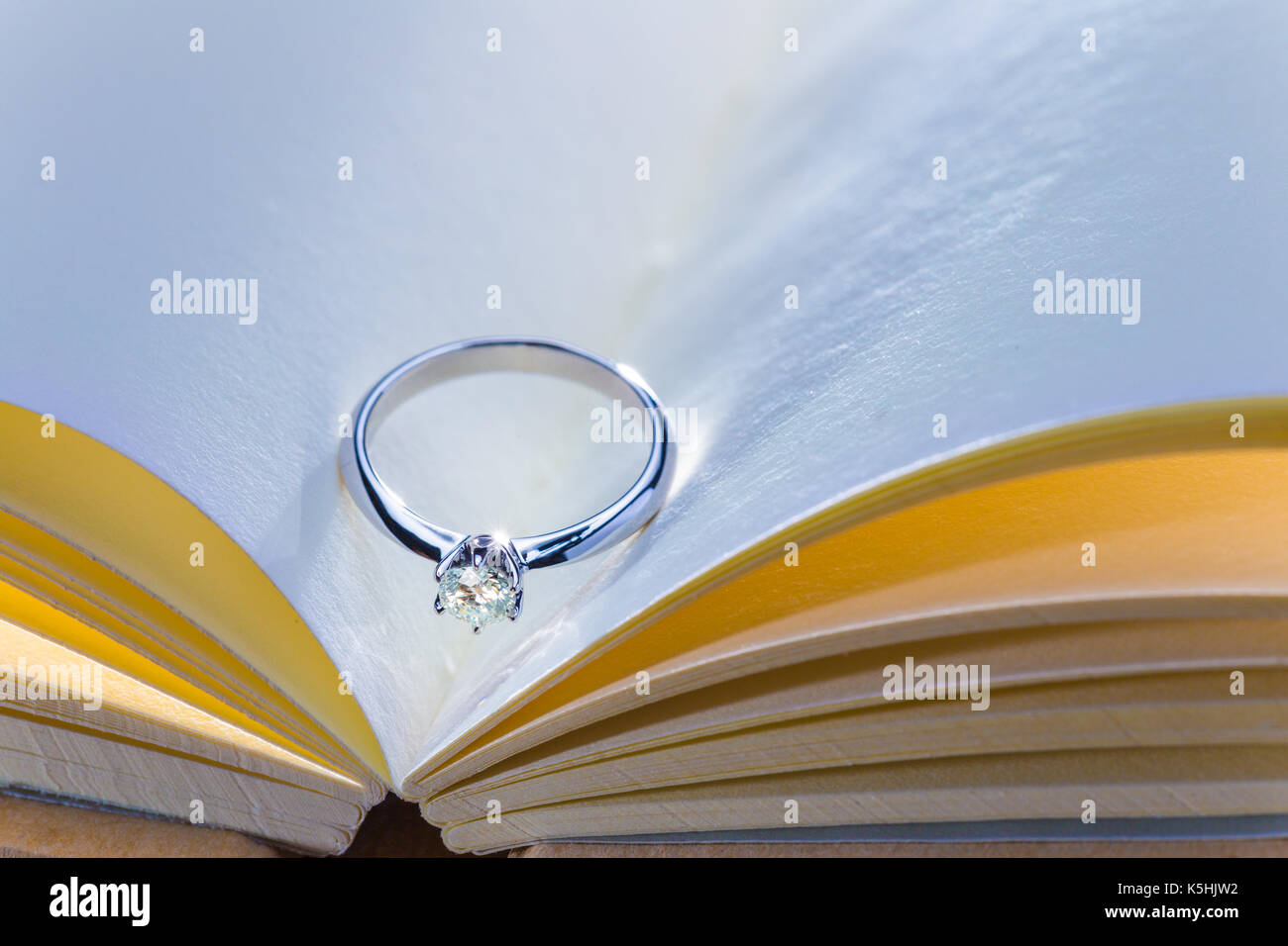 beautiful diamond ring on blank open book with cool and warm color ...