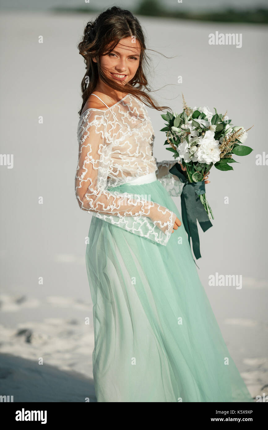 Bride In Wedding Dress Stands And Smiles In Desert With Bouquet In