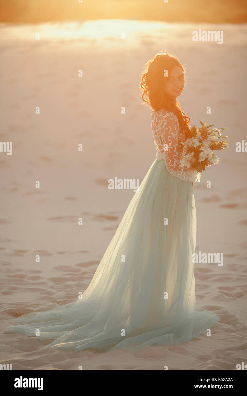 Bride In Long Wedding Dress With Bouquet Stands On Sand In Desert