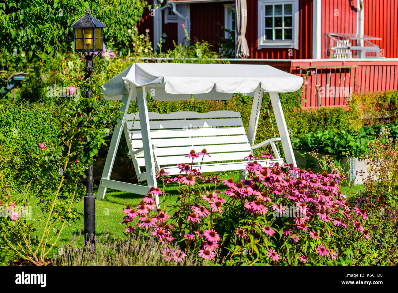 Empty White Canopy Swing Or Patio Swing In Green Flower Garden. Lamppost  And Flowers In