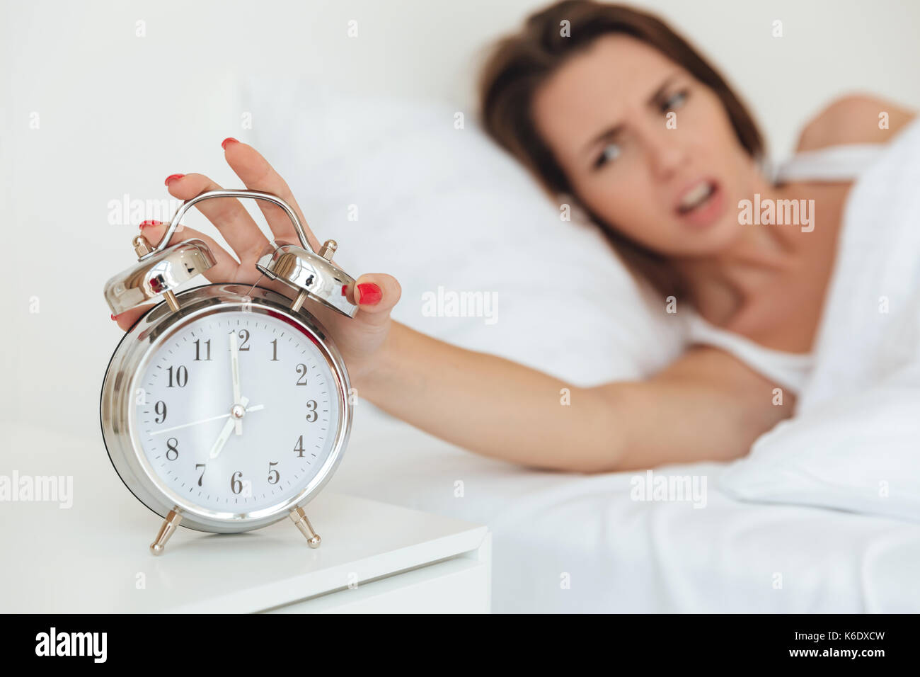 Close Up Of A Woman Turning Off Alarm Clock In The Morning While Laying In Bed