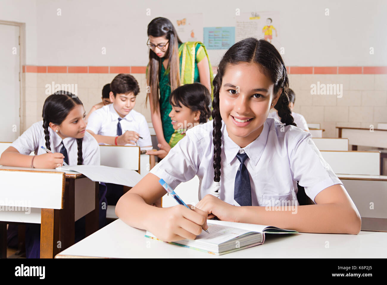 smiling 1 school girl student writing note book studying in
