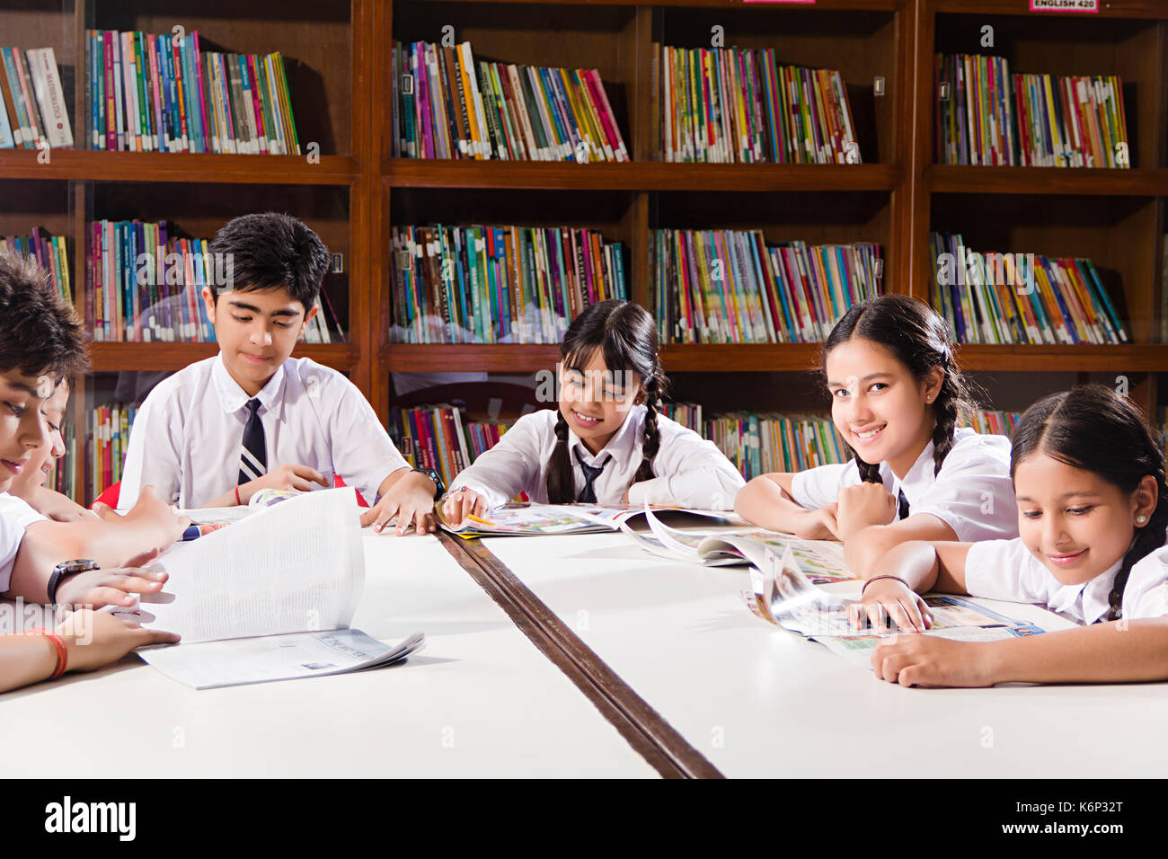 group indian school kids students books studying in library stock