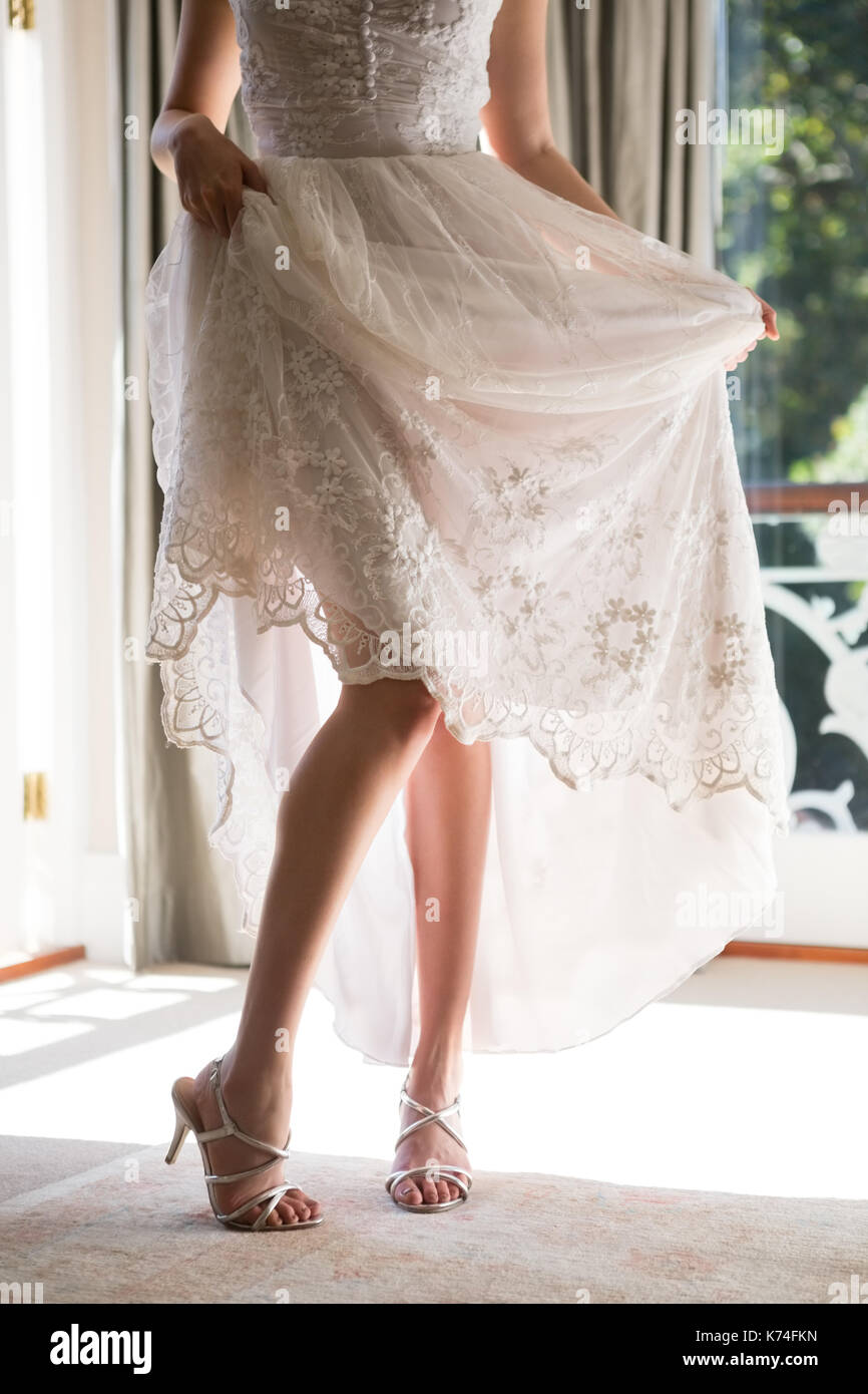 Low Section Of Bride In Wedding Dress And Sandals Standing On Floor