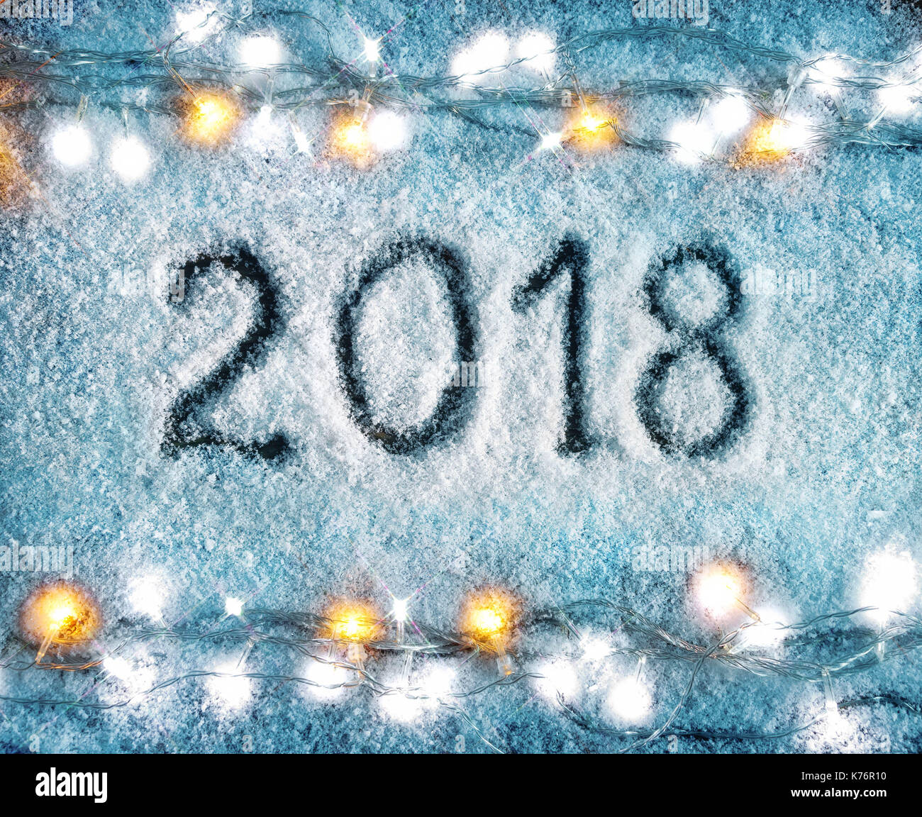merry christmas and happy new year snowy background with garland and the inscription 2018 top view high resolution product