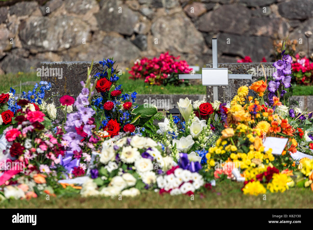 Lots Of Flowers And Small Cross After A Funeral At A Cemetery Name