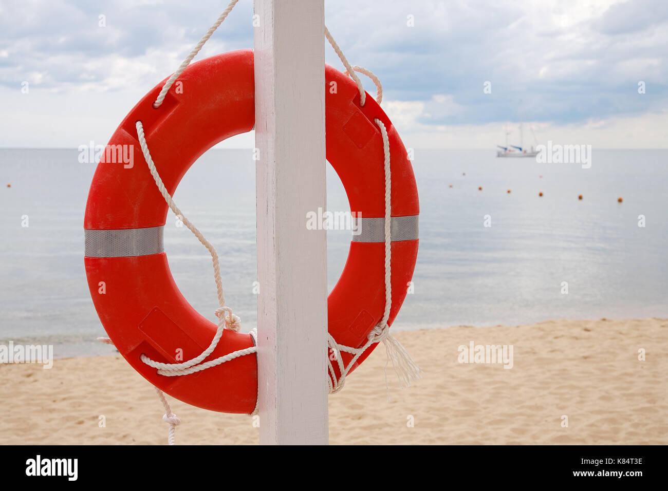 Welcome aboard boat ships life ring clock - Life Ring Hanging On A Pillar On The Beach Against The Sea Stock Image