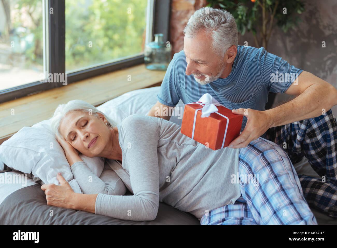 Cheerful Elderly Man Preparing A Birthday Present For His Wife