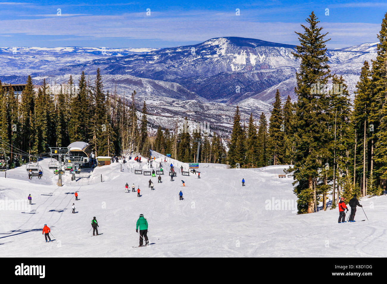 view of a colorado ski resort on a nice winter day; skiers and stock