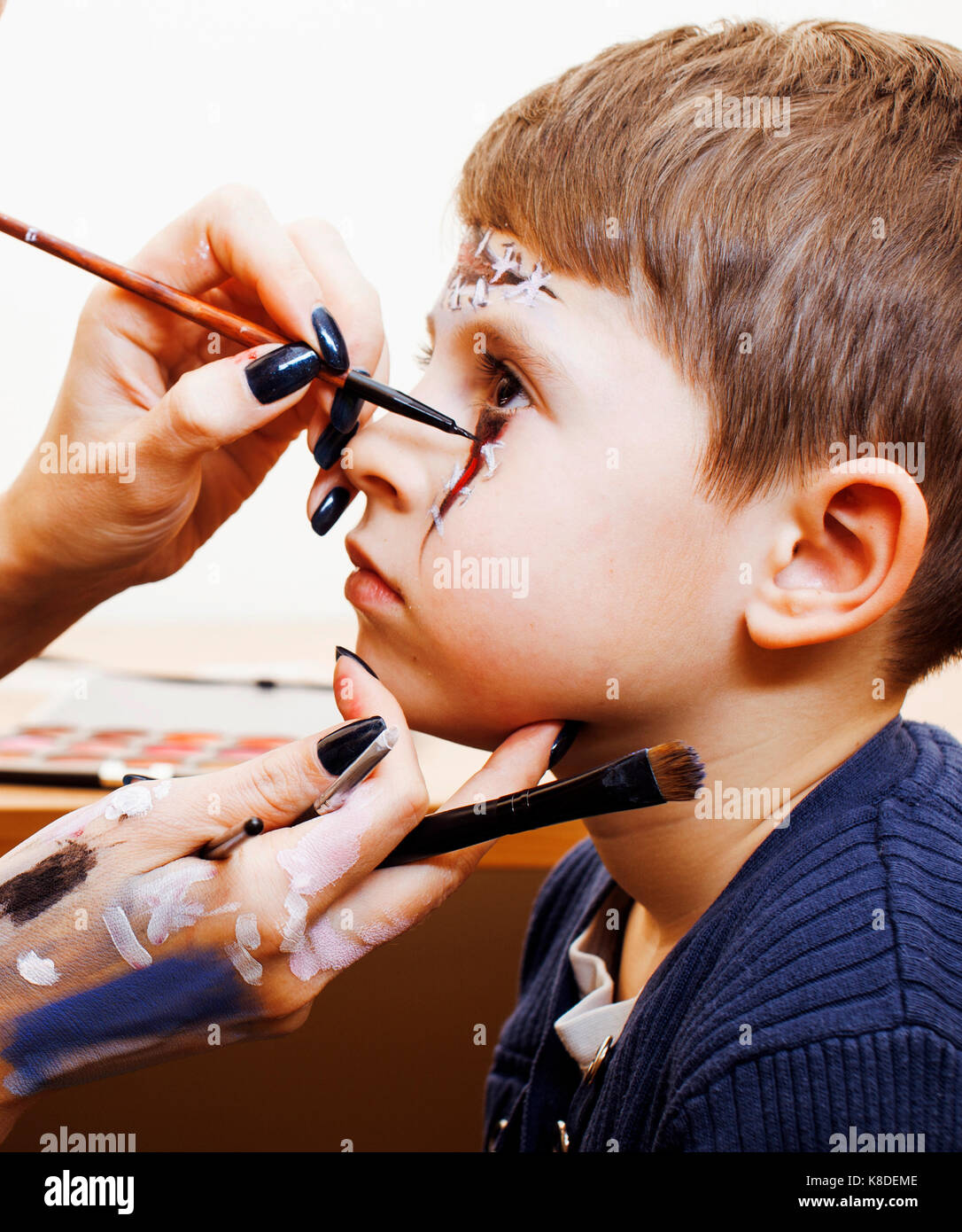 little cute child making facepaint on birthday party zombie Apo