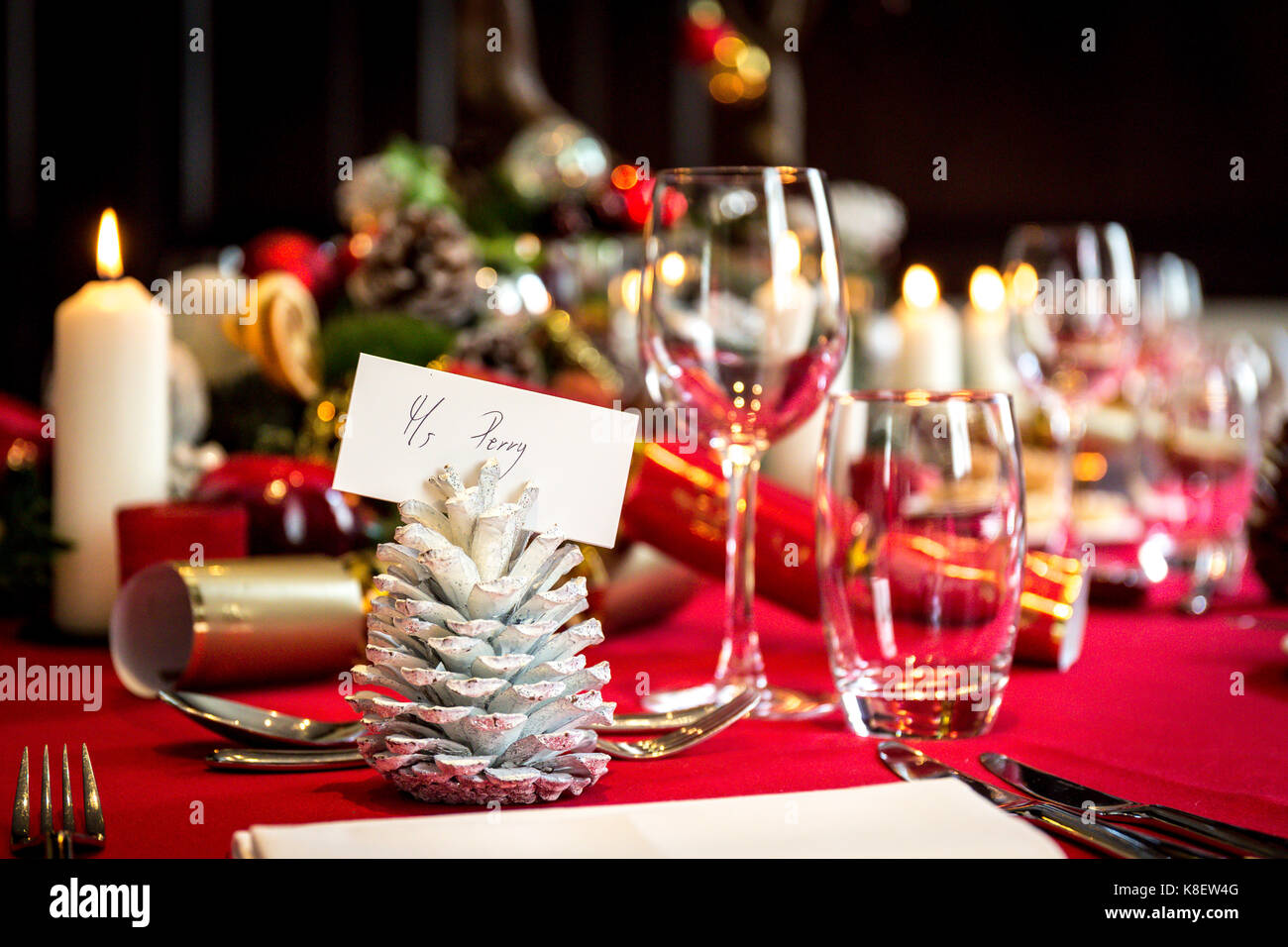 Dining table set for christmas lunch with place settings, decorations and  candles