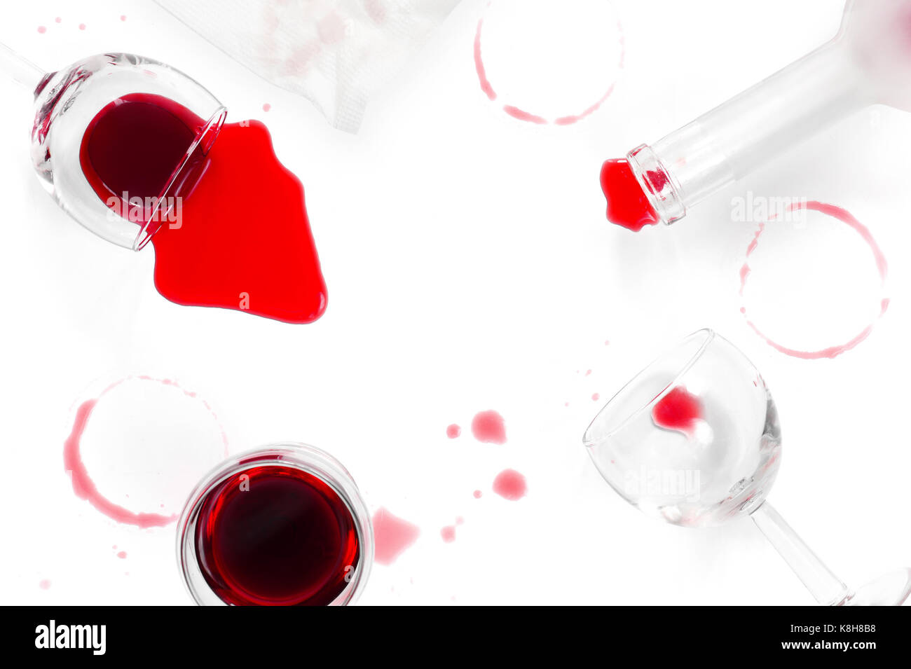 spilled red wine glasses and a bottle on the white table stock