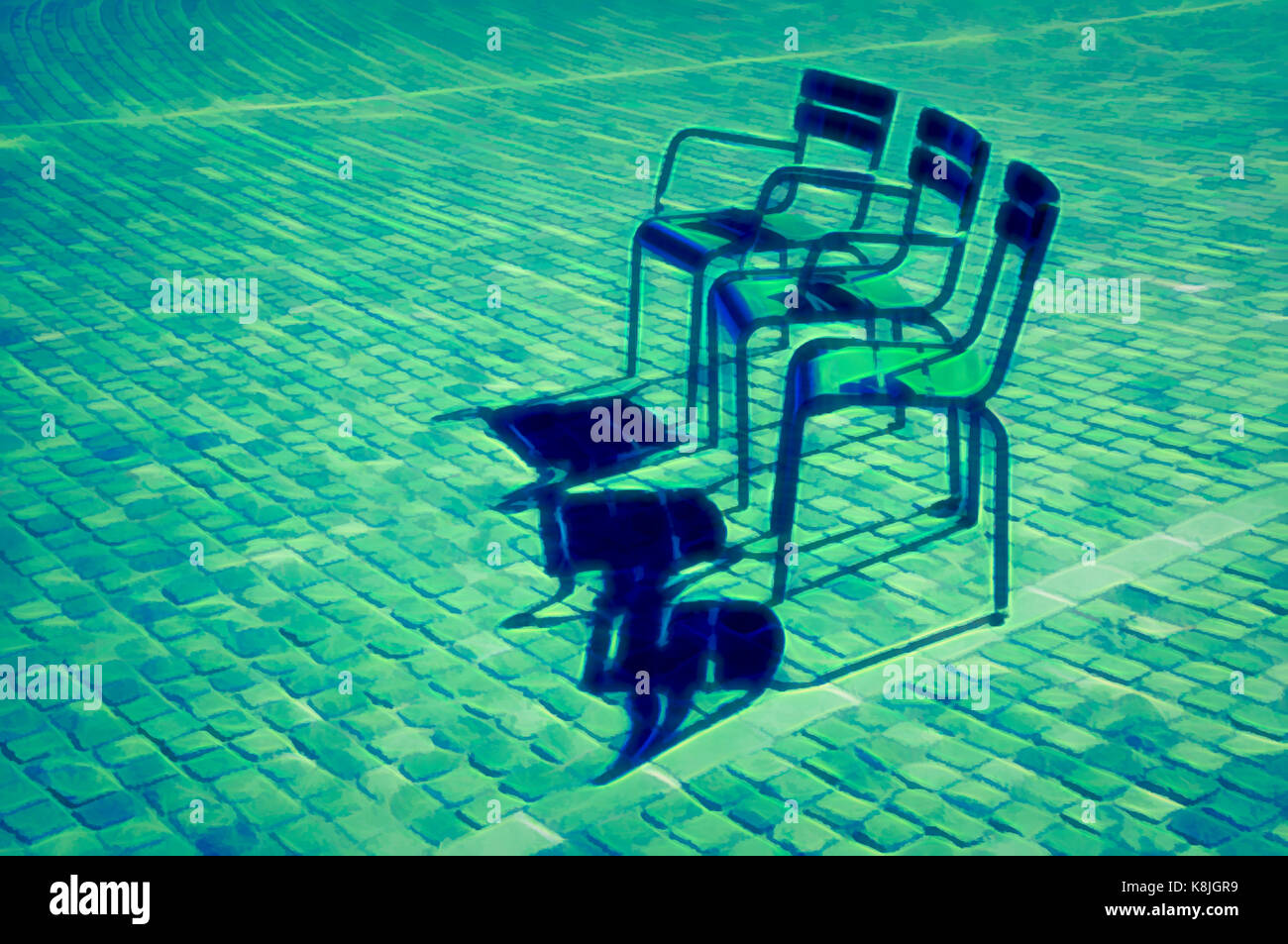 Chairs On A Cobblestone Square   Stock Image