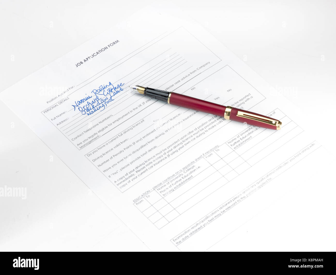 A Fountain Pen With Partially Filled Out Job Application Form Stock