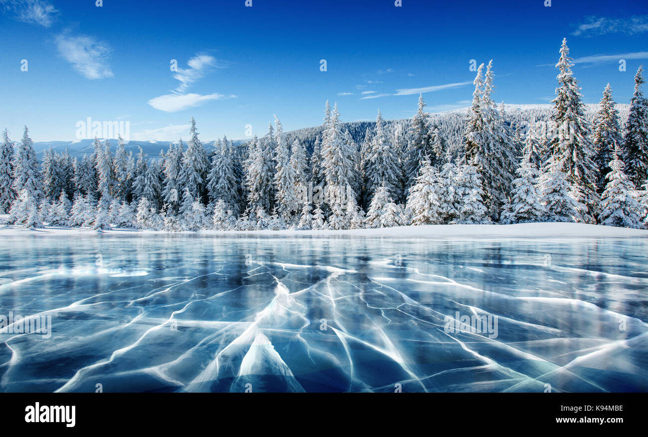 blue ice and cracks on the surface of the ice frozen lake under a