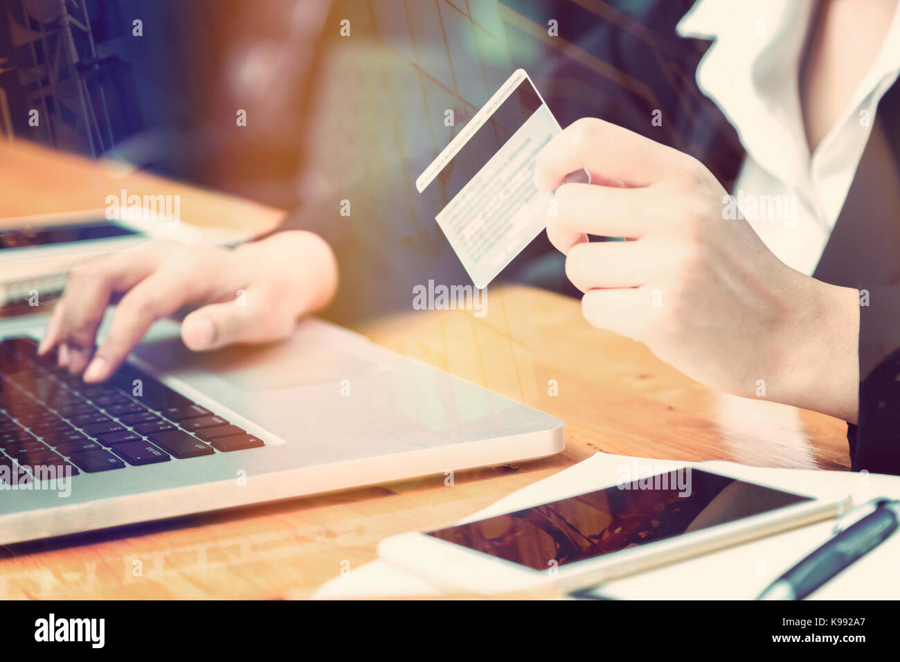 Female hand of business woman holding credit card making purchase female hand of business woman holding credit card making purchase online with window reflection and lens flare effect good for business ecommerce con colourmoves