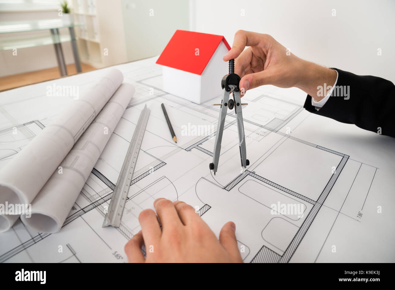 Close up of male architect using compass on blueprint paper stock close up of male architect using compass on blueprint paper malvernweather Images