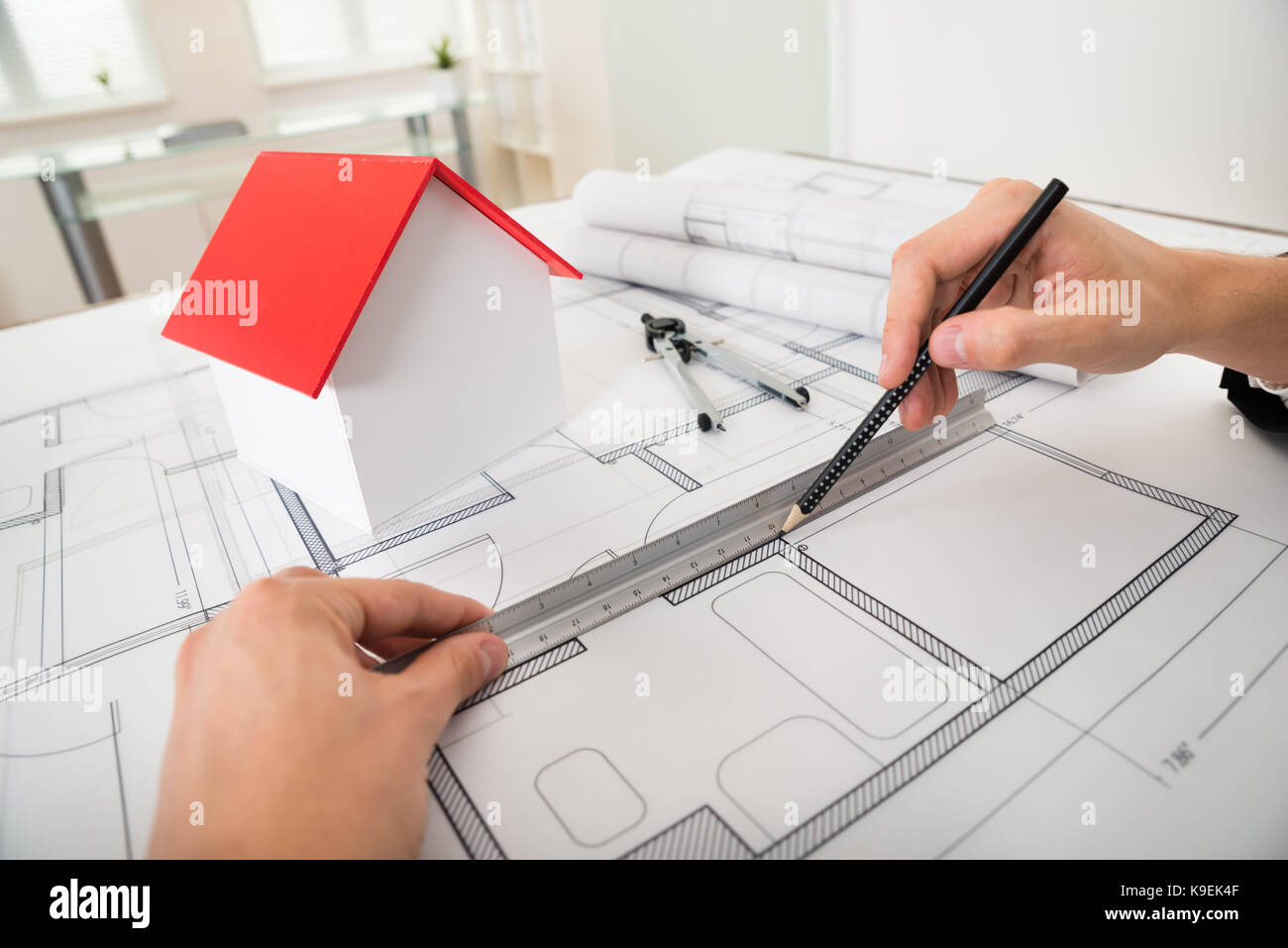 Close up of engineer drawing diagrams in front of house model on close up of engineer drawing diagrams in front of house model on blueprint malvernweather Choice Image