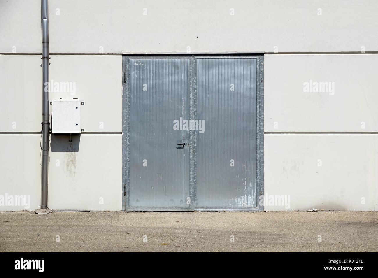 White Overhead Steel Garage Door On Exterior Of Beige Metal Building With  Red Bumper Posts .
