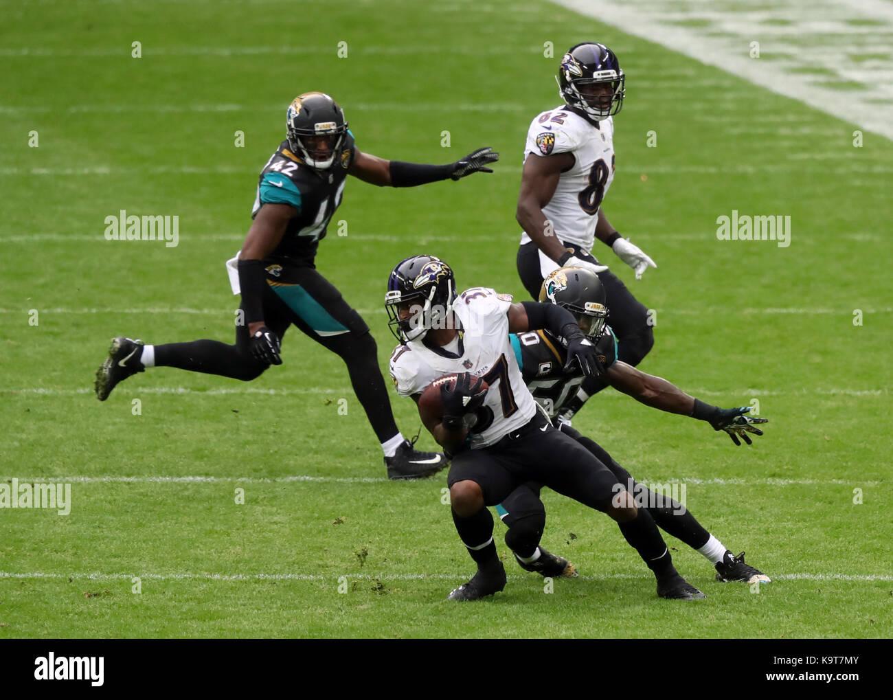 Baltimore Ravens Javorius Allen is tackled by Jacksonville Jaguars