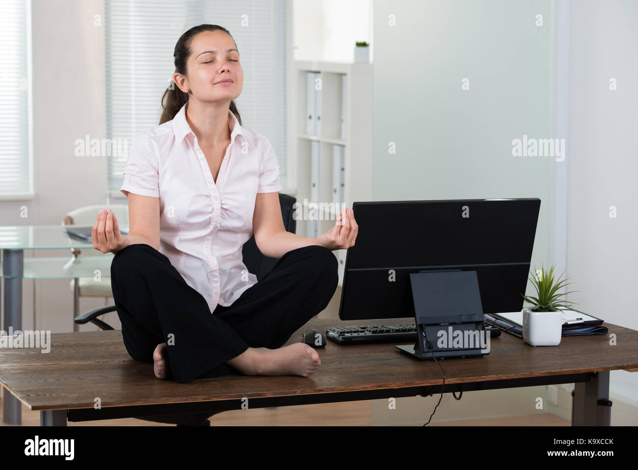 Young Businesswoman Doing Meditation On Desk In Office
