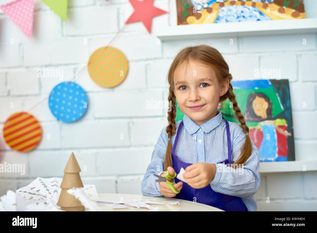 Portrait Of Pretty Little Girl Smiling Happily At Camera While Making Handmade Christmas Decorations During Art And Craft Class Pre School Copy Sp