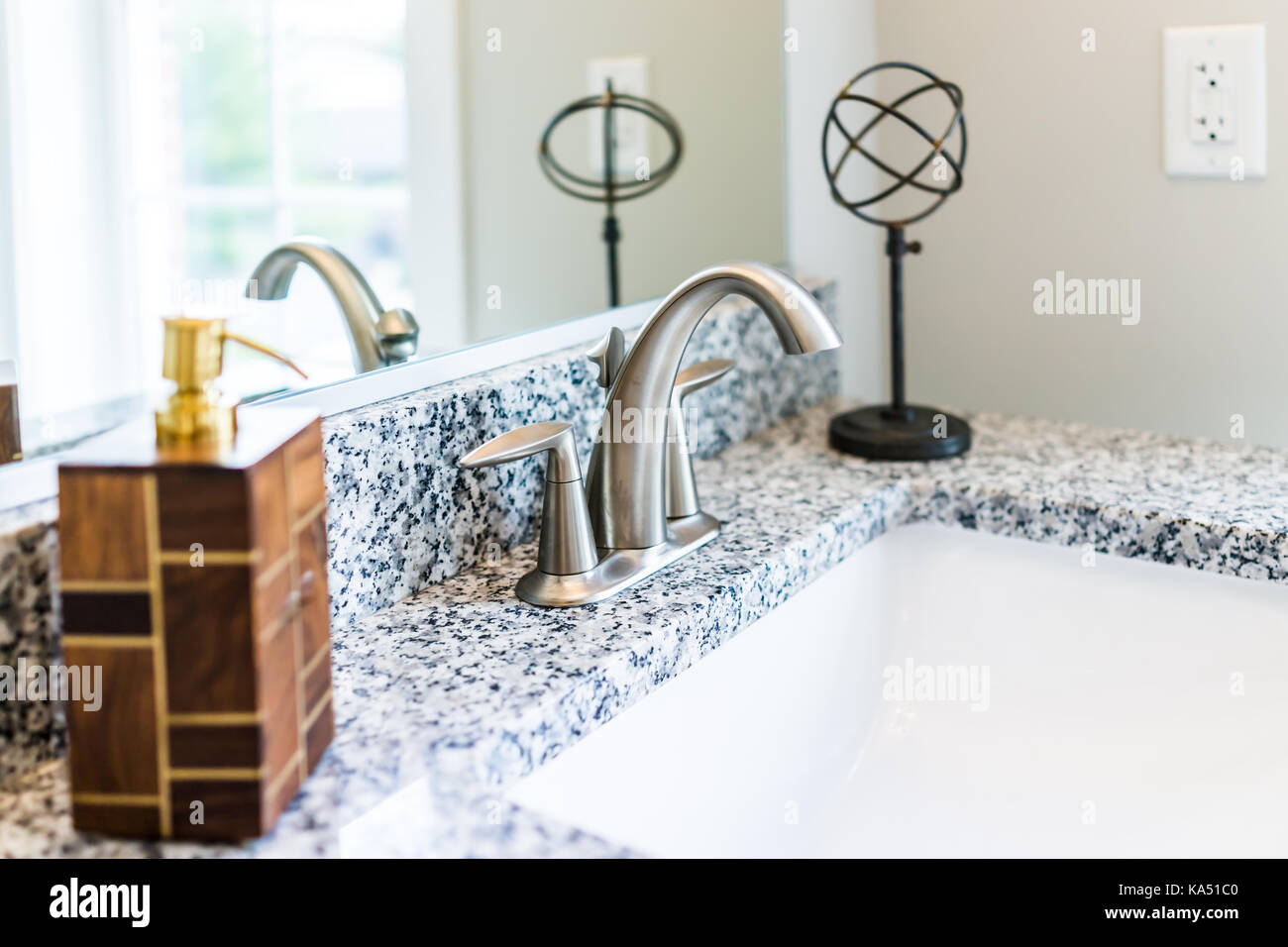Closeup of modern bathroom sink with granite countertop, mirror ...