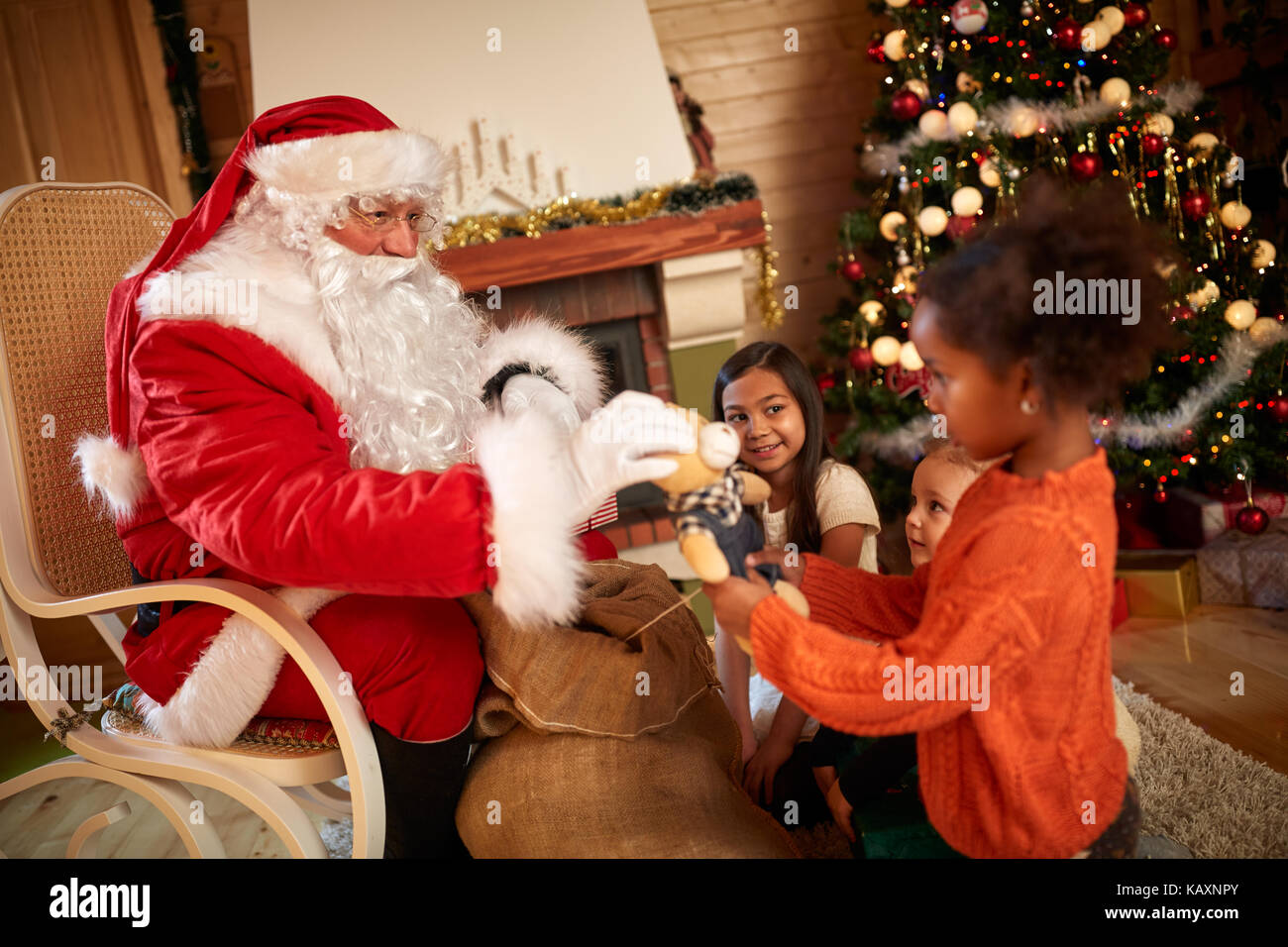 Santa claus giving gifts to children in their living room stock santa claus giving gifts to children in their living room negle Choice Image