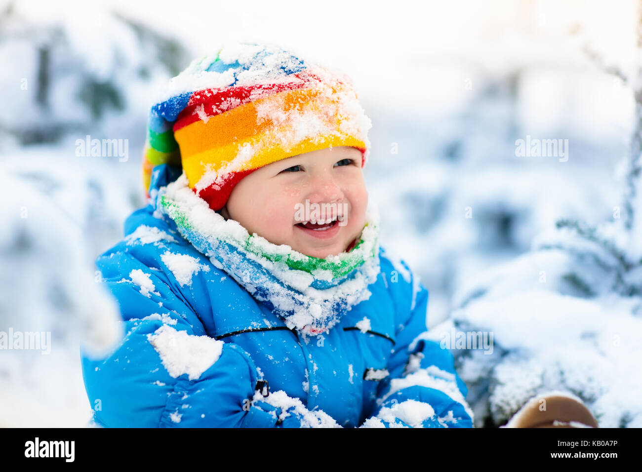 Baby playing with snow in winter. Little toddler boy in blue ...