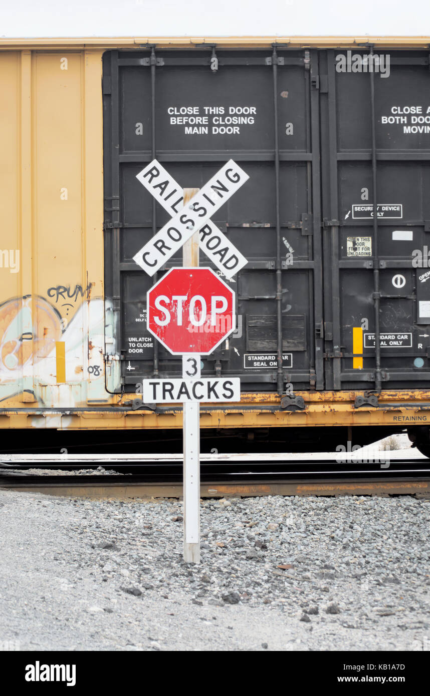 a rail road crossing sign in front of a moving railroad trailer