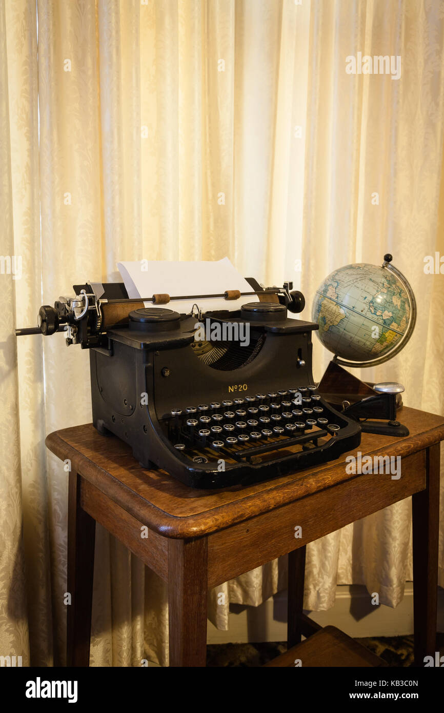 Antique typewriter, globe and stapler on a desk - Antique Typewriter, Globe And Stapler On A Desk Stock Photo, Royalty