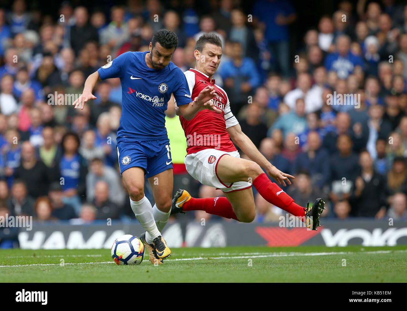 Laurent Koscielny of Arsenal slides in to tackle Pedro of Chelsea